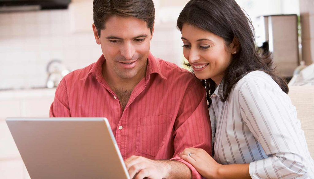 happy couple looking at a laptop