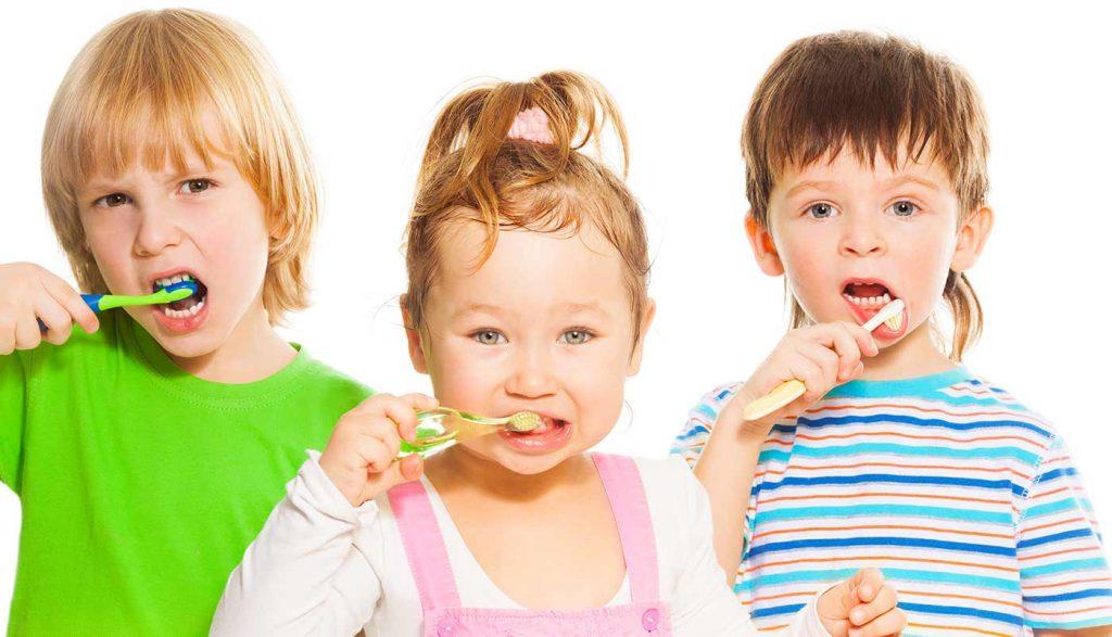 three young kids brushing their teeth